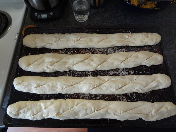 Baguettes placed on the baking sheet and scored with a knife